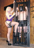 Caged and masked slave and cruel domina